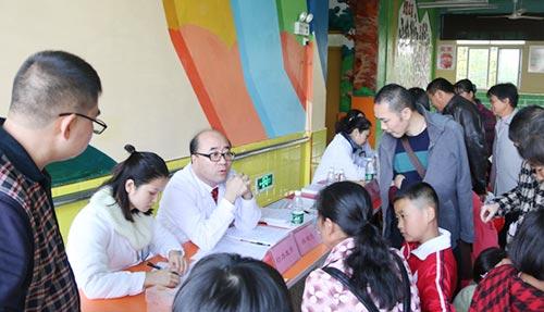 医务人员为孩子们进行公益体检及家长咨询